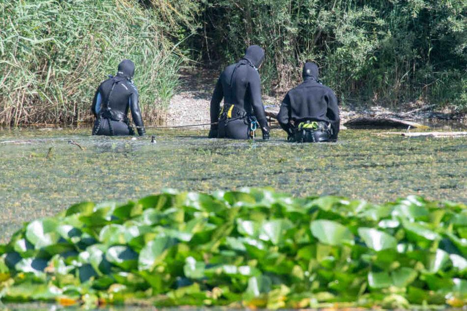 Taucher der Polizei suchen im Baggersee im alten Kieswerk bei München nach zwei Leichen.