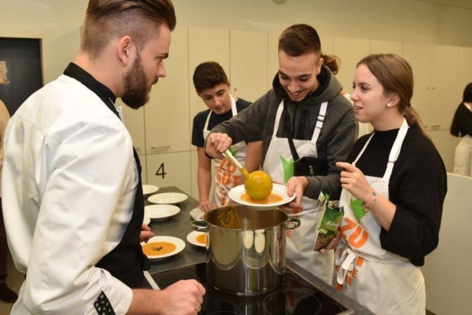 Jungkoch mit jugendlichen Kochkursteilnehmern.