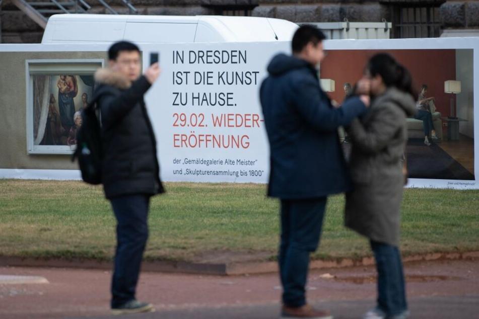 Touristen stehen im Zwinger vor einem Bauzaun des Semperbaus mit der Gemäldegalerie Alte Meister.