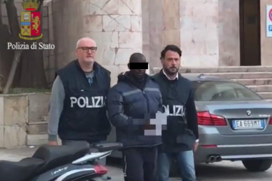 Der Mann wird von Polizisten abgeführt! Seine Opfer hatten ihn auf offener Straße wiedererkannt.