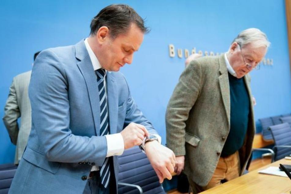 Tino Chrupalla (l.), AfD-Bundessprecher, blickt neben Alexander Gauland, Fraktionsvorsitzender der AfD, in der Bundespressekonferenz auf seine Uhr.