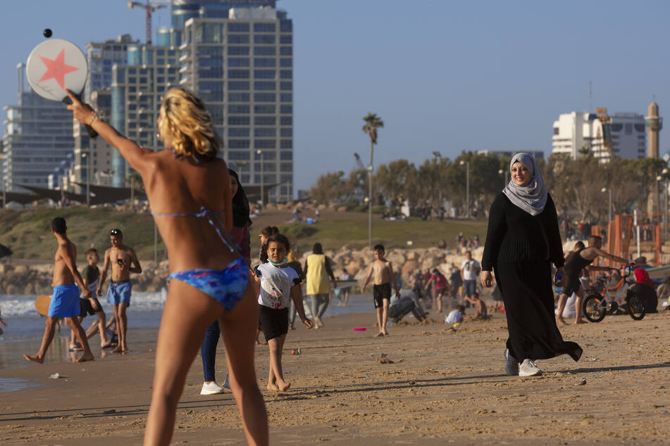 Palästinenser und Israelis genießen die Sonne am Mittelmeer während des Feiertags Eid al-Fitr am 25. Mai. Eid al-Fitr markiert das Ende des Fastenmonats Ramadan. Die Feierlichkeiten wurden wegen des Coronavirus-Ausbruchs eingeschränkt.
