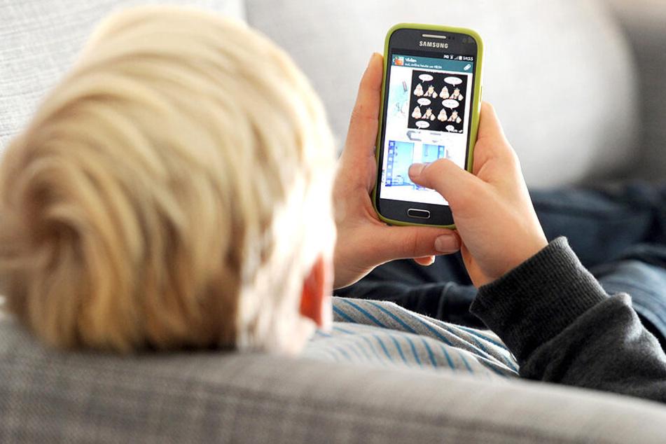 Ein Schüler spielt mit seinem Handy. Per Mobiltelefon erhielten einige Jugendlichen auch sexy Schnappschüsse von ihrer Lehrerin.