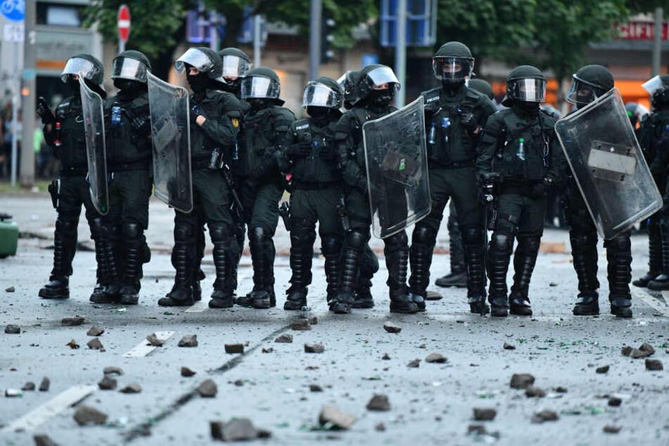 Polizisten stehen am 07.07.2017 in St. Pauli in Hamburg vor Steinbrocken und Glasscherben.