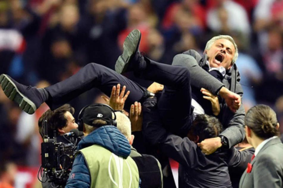 So glücklich sieht Trainer José Mourinho nicht aus, als ihn seine Spieler in die Höhe werfen.