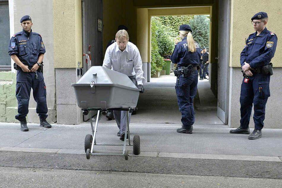 Die Leiche des getöteten Mädchens wird in einem Sarg aus einer Wohnhausanlage in Wien gebracht und in einen Leichenwagen gehoben.