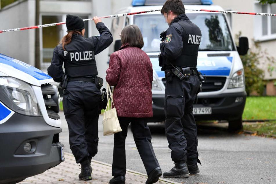 Polizisten begleiten eine Frau. Am Sonntagmittag wurden wieder Teile eines Wohngebiets abgesperrt.