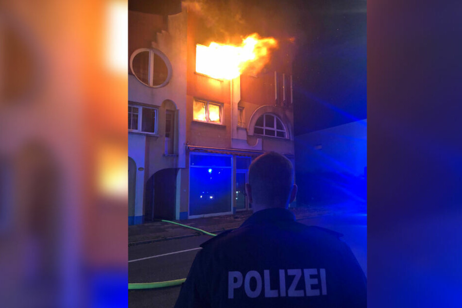 Ein Polizist steht vor dem Wohnhaus, aus dem meterhohe Flammen schlagen.
