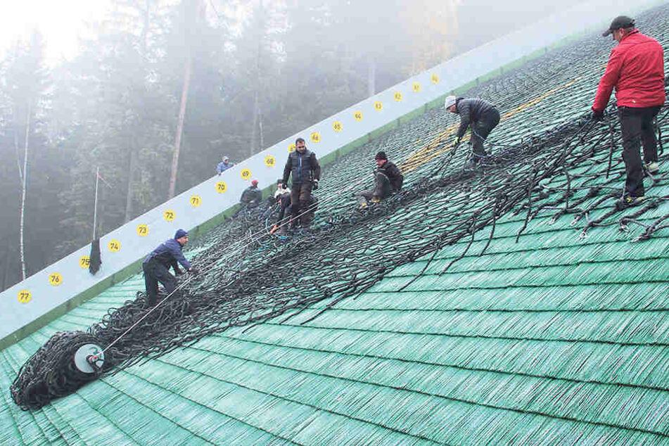 Mitarbeiter der Sparkasse Vogtland Arena und etliche Helfer brachten die Schneehaltenetze auf dem Absprunghang an.