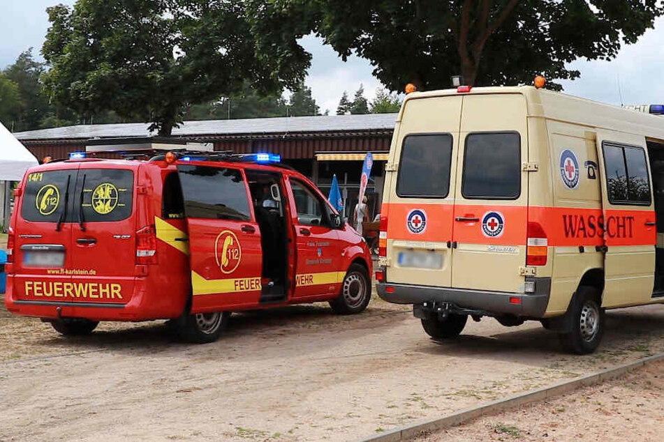 Ein Wagen der Feuerwehr und der Wasserwacht stehen am Eingang des Badesees.