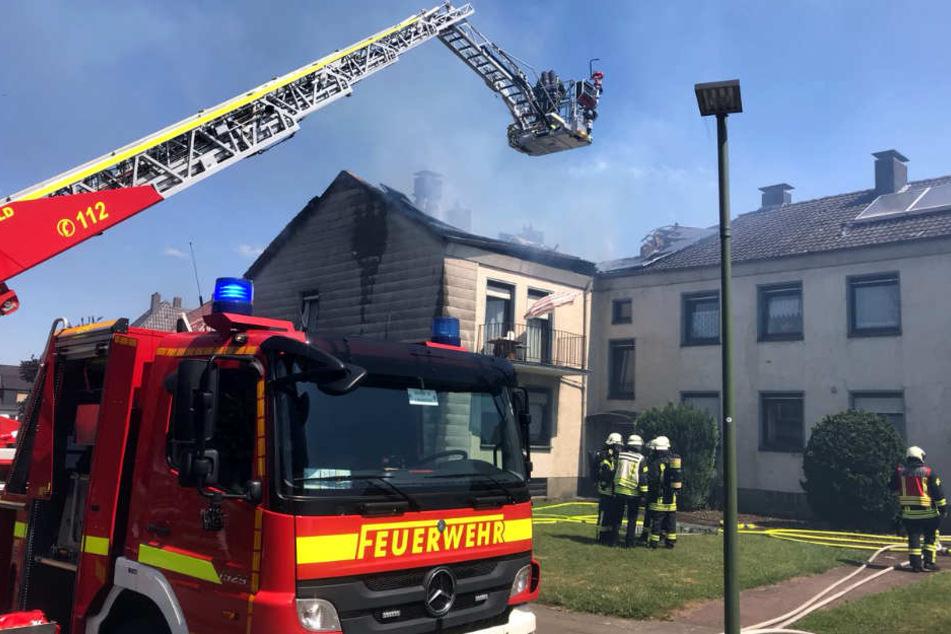 Mit einer Drehleiter kämpft die Feuerwehr gegen die Flammen im Dachstuhl.