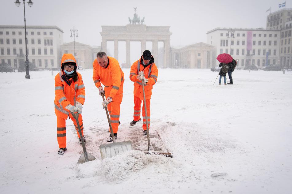 Mitarbeiter der Berliner Stadtreinigung schaufeln den Schnee am Brandenburger Tor vom Gehweg.