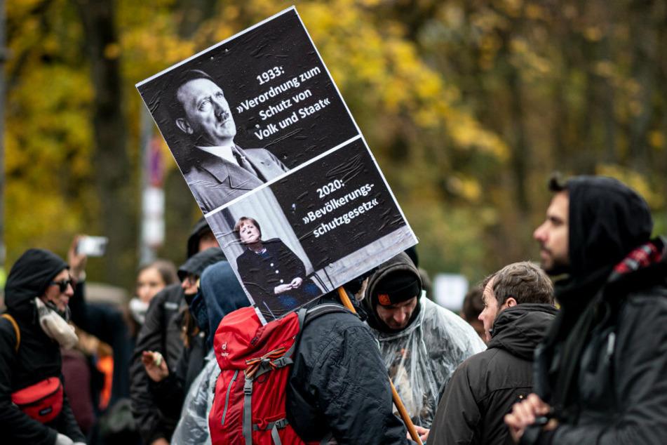 Ein Teilnehmer der Demonstration gegen die Corona-Einschränkungen hält ein Schild hoch auf dem unter Adolf Hitler Angela Merkel abgebildet ist.