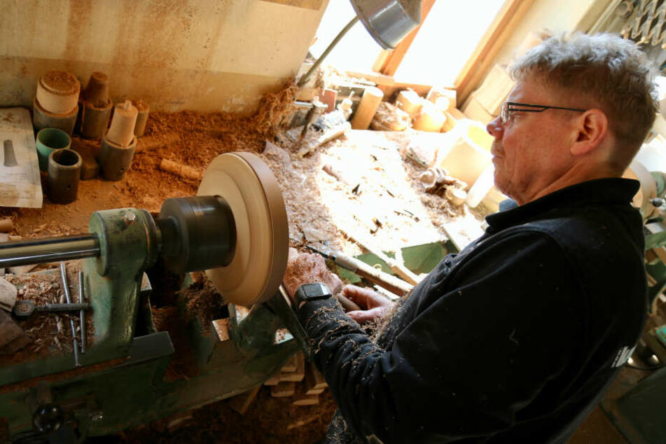 Drechslermeister Jens König steht in seiner Werkstatt an einer Drehbank und fertigt einen Schmuckteller aus Nussbaum, in dem Halsketten oder Armbänder präsentiert werden.