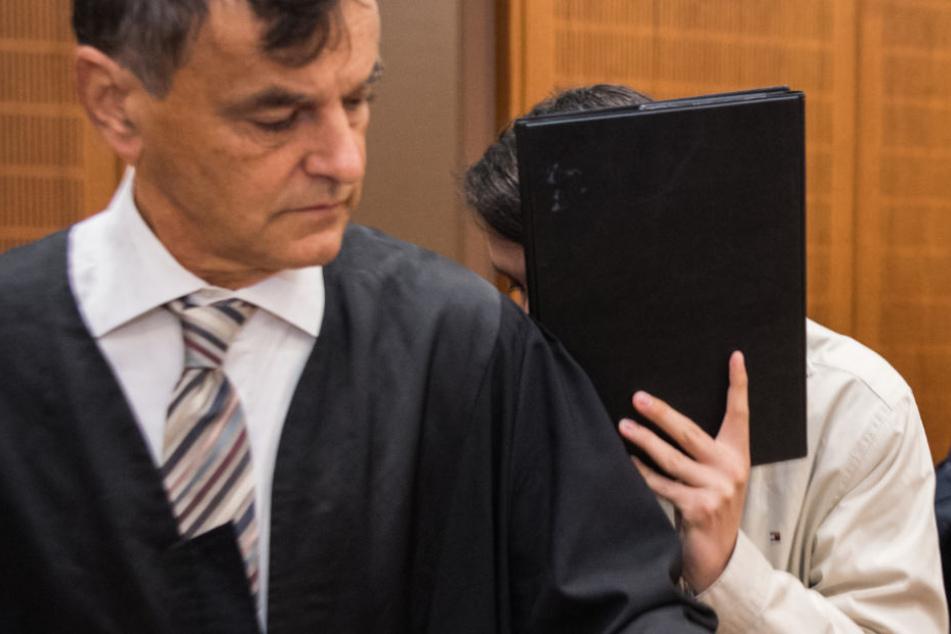 Der Angeklagte versteckt sich hier hinter einer schwarzen Mappe.