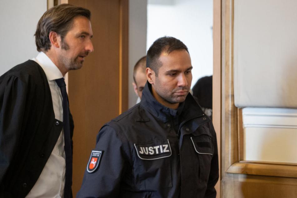 Verteidiger Frank Otten (l) blickt auf seinen Mandanten (2.v.r, verdeckt) der von Justizbeamten in den Gerichtssaal geführt wird.