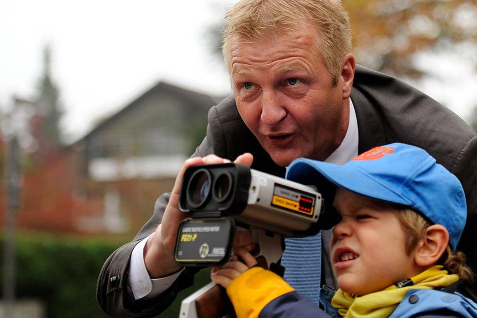 Hier zeigt NRWs-Innenminister Ralf Jäger (SPD) einem Kind, wie Polizisten beim Blitz-Marathon messen.