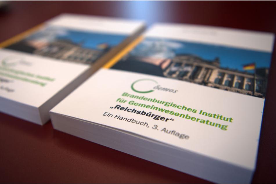 Handbücher zum Umgang mit den sogenannten Reichsbürgern liegen während einer Pressekonferenz im Brandenburger Innenministerium auf einem Tisch.