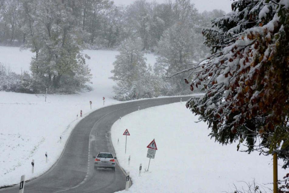 Ein Auto fährt durch die Schneelandschaft.
