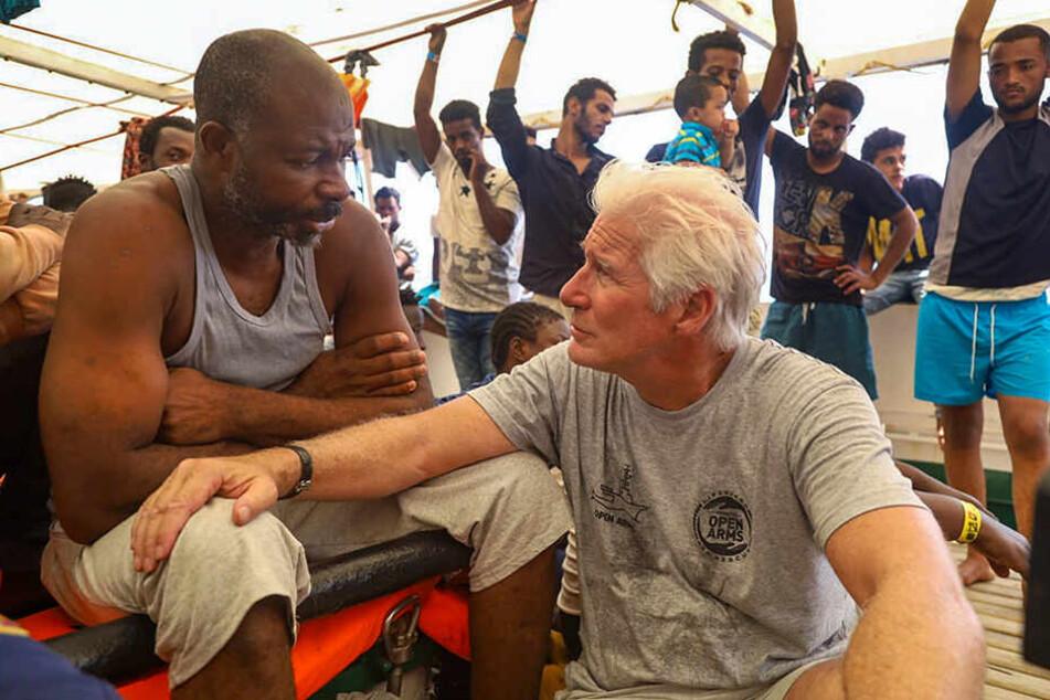 """Richard Gere (re.) spricht mit einem Migranten an Bord des spanischen Rettungsschiffs """"Open Arms"""" der Hilfsorganisation Proactiva Open Arms, das im Mittelmeer kreuzt."""