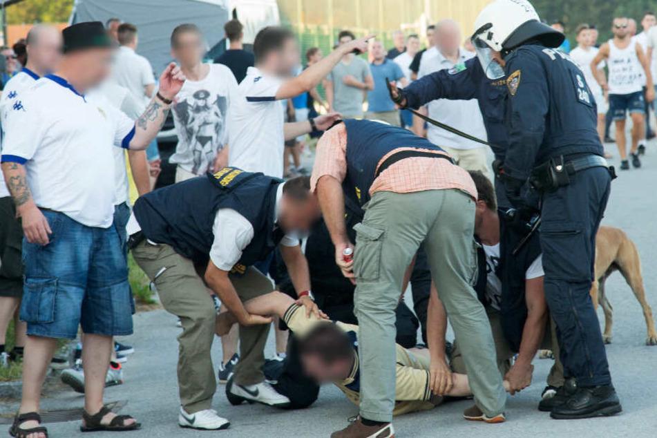 Ein Mann liegt auf dem Boden, während ihn Einsatzkräfte festhalten.