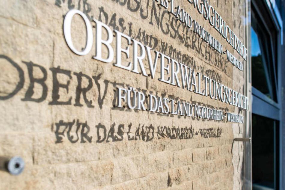 Münster: An der Außenfassade des OVG hängt eine Hinweistafel mit dem Landeswappen von NRW