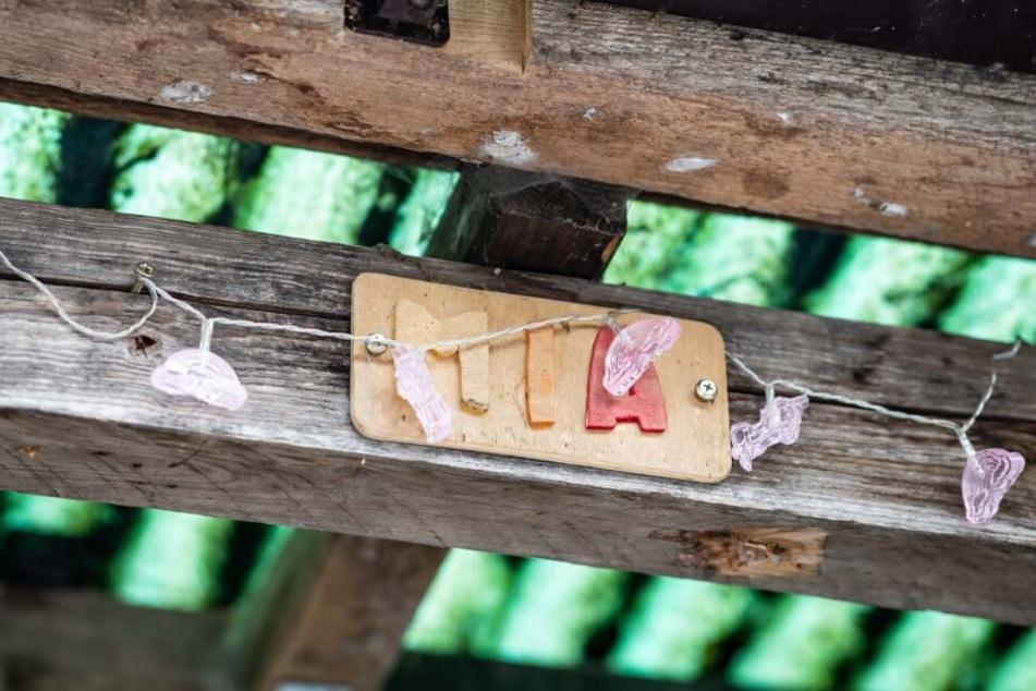 """An einem Balken über einer Tür hängt ein Schild, auf dem der Name """"Mia"""" steht."""