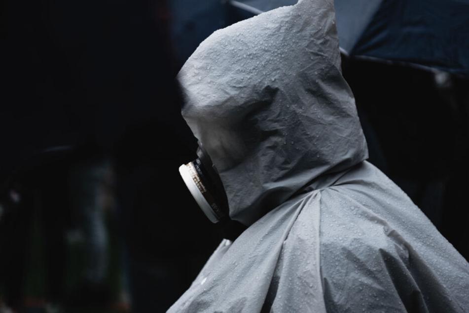 Ein Demonstrant trägt eine Atemschutzmaske während einer Kundgebung (Symbolbild).