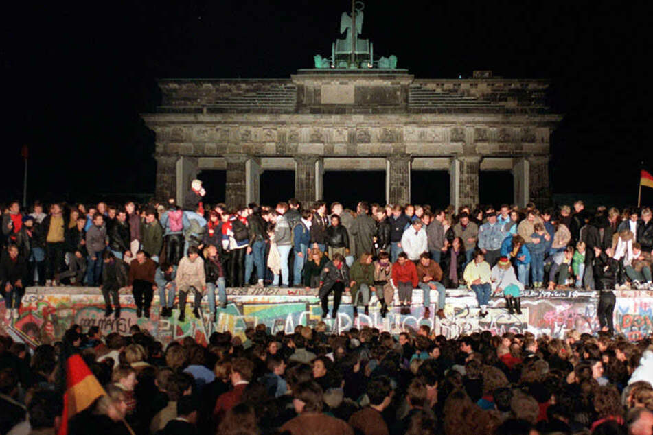 Jubelnde Menschen stehen auf der Berliner Mauer am Brandenburger Tor am. Die BerlinerMauer stand 28 Jahre, 2 Monate und 26 Tage.