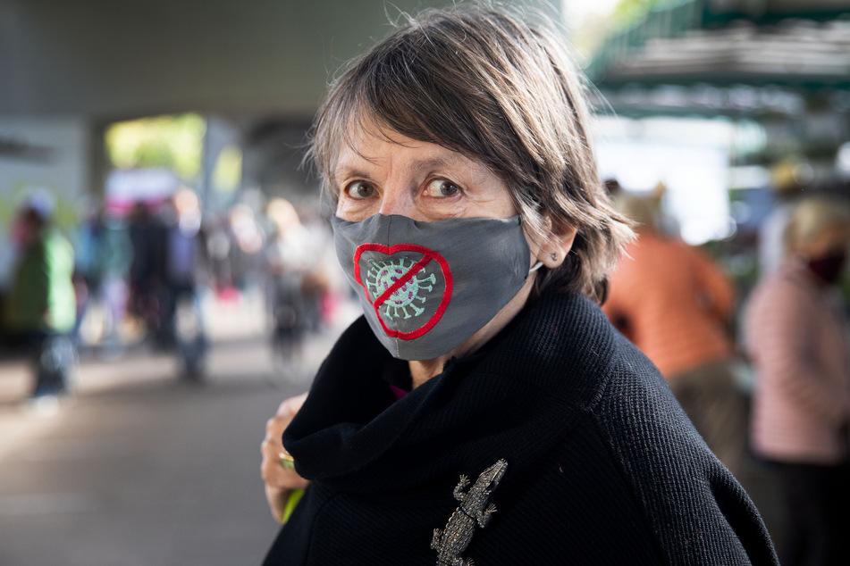 Eine Frau trägt einen Mund-Nasen-Schutz mit einem eingestickten Corona-Virus.