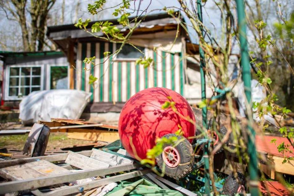 Ein Kindertretauto und ein Hüpfball liegen vor der bereits zum Teil abgerissenen Parzelle des mutmaßlichen Täters.