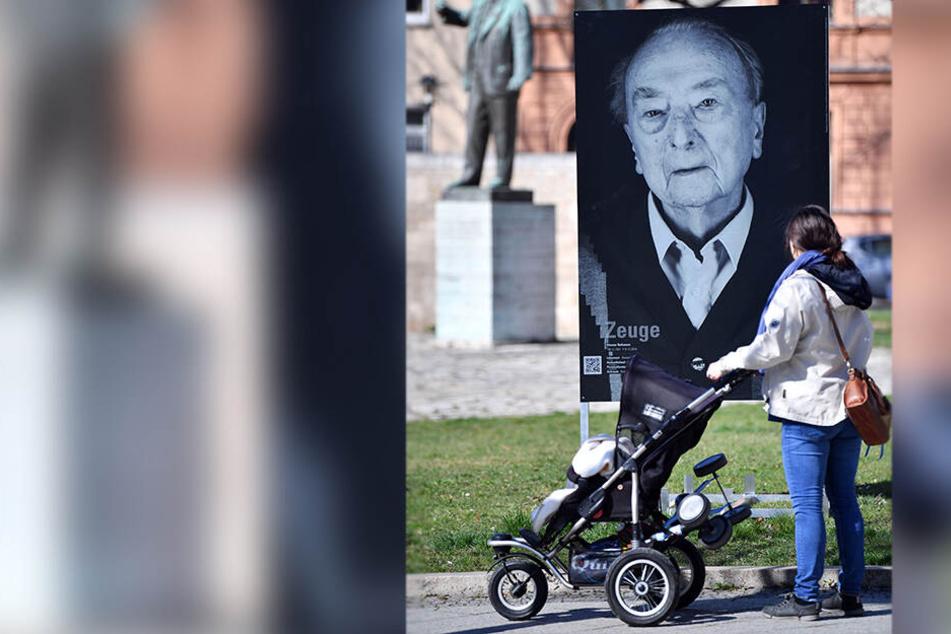 Mann spuckt, tritt und pinkelt gegen Foto von KZ-Überlebenden