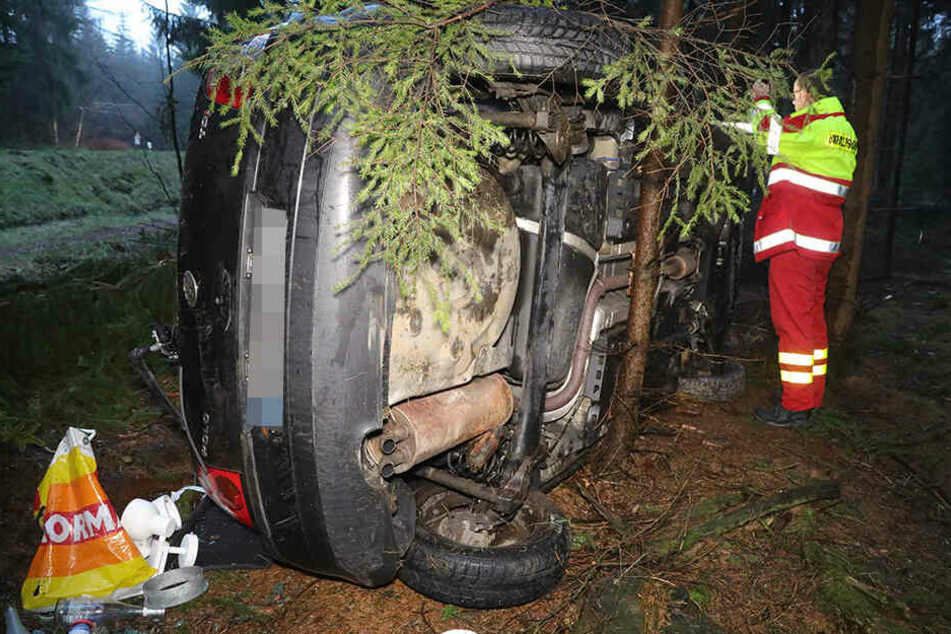 Ein Mitarbeiter der Unfallforschung untersucht den VW, der zwischen den Bäumen auf der Fahrerseite zum Stehen kam.