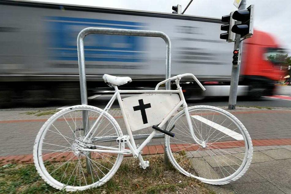 Ein weißes Fahrrad mit einem schwarzen Kreuz erinnert an einer Ampelkreuzung an einen Fahrradunfall mit tödlichen Ausgang.