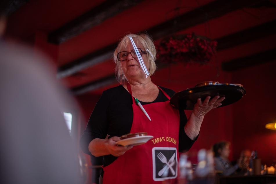 Die Inhaberin einer spanischen Tapas Bar serviert ihren Gästen Speisen und trägt dabei ein Schutzvisier.