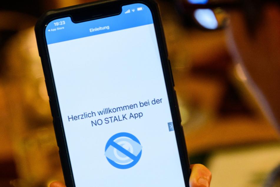 Eine Frau hält ein Smartphone mit geöffneter Stalking-App des Weißen Rings.