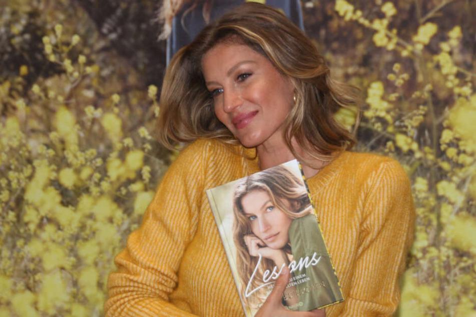 """Topmodel Gisele Bündchen hält ihr Buch """"Lessons"""" in den Händen."""