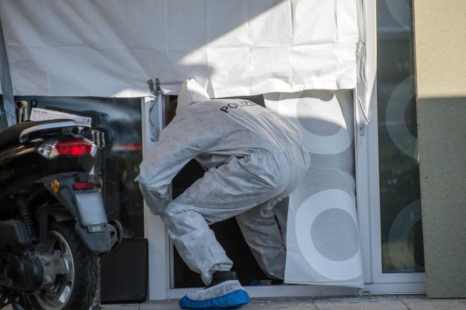 Ein Mitarbeiter der Spurensicherung der Polizei betritt ein Haus, in dem mehrere Tote gefunden wurden.