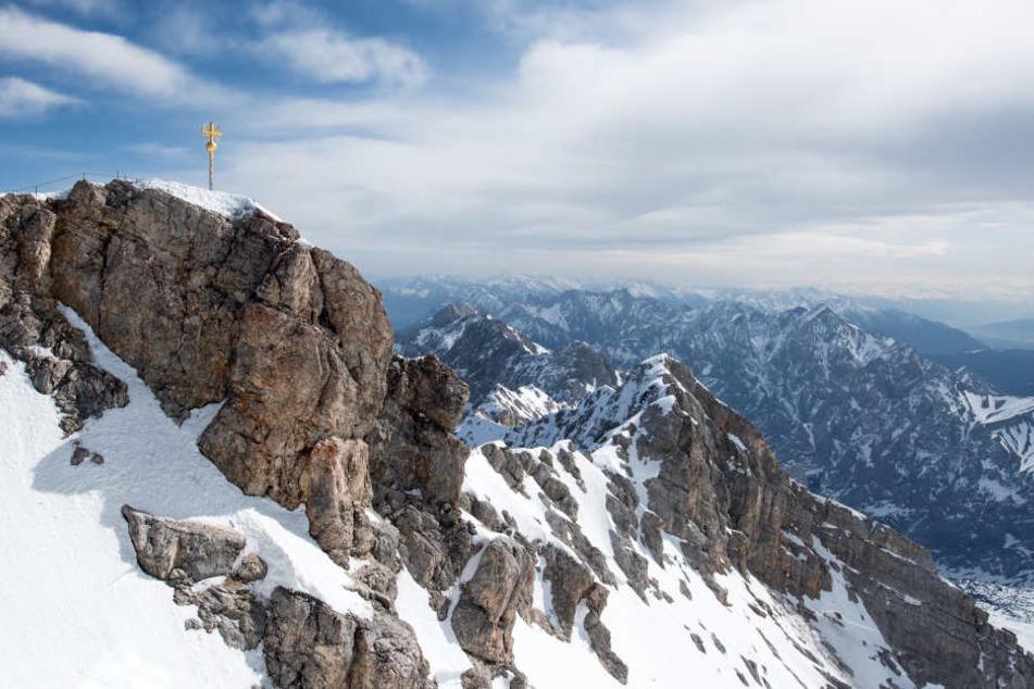 Die Sonne scheint im bayerischen Garmisch-Partenkirchen über dem Gipfelkreuz auf der Zugspitze.