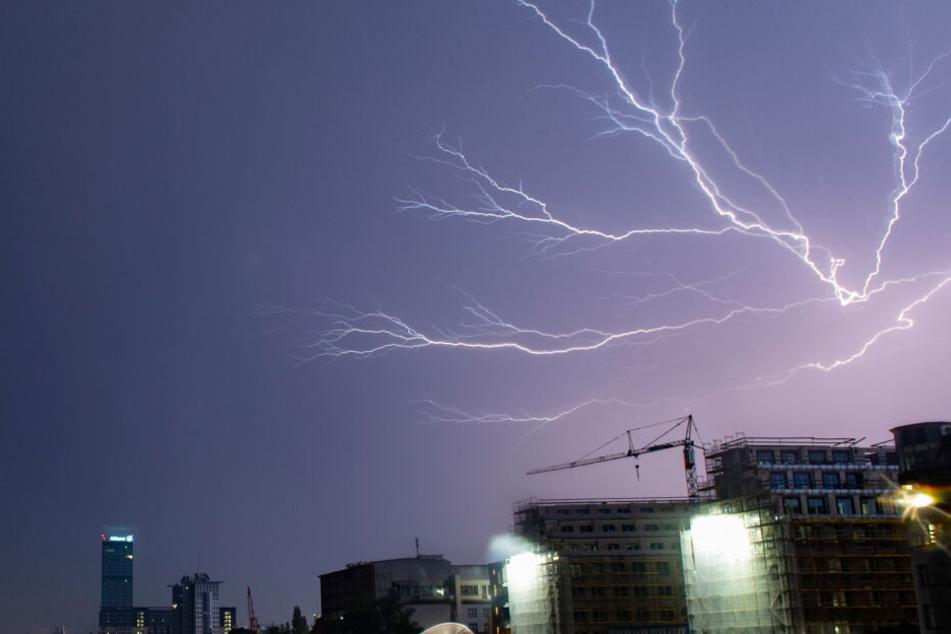Blitze zucken während eines Gewitters unweit des Allianz-Hochhauses in Berlin über den Himmel.