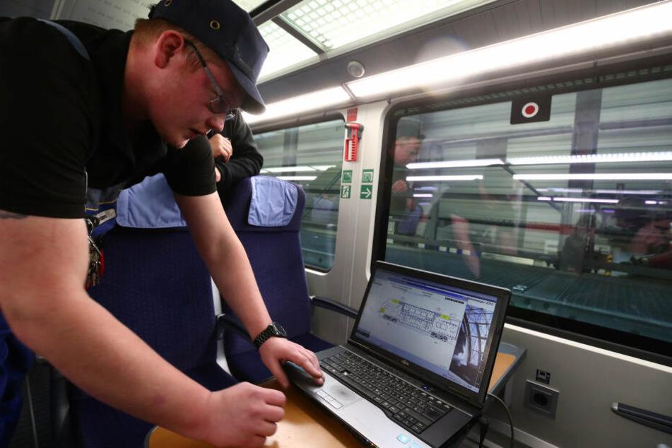 Markus Aßmann überprüft an einem Laptop die Heizungsanlage in einem IC im Leipziger ICE-Werk bei der Inspektion und Wintervorbereitung.