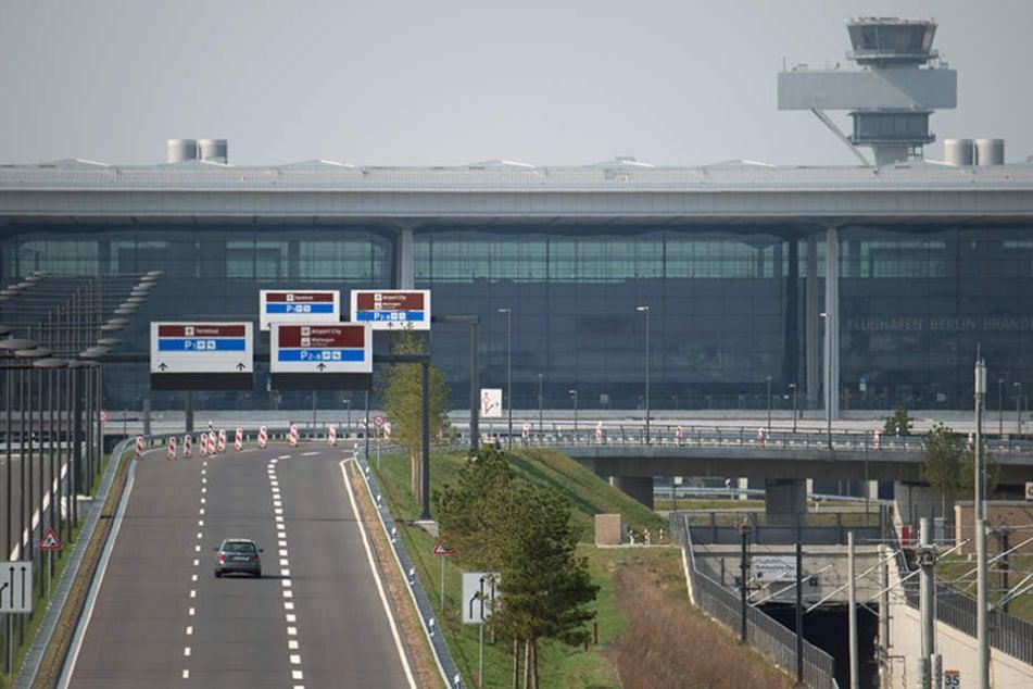 Ein Auto fährt auf der Zufahrtsstraße des Flughafens Berlin Brandenburg Willy Brandt (BER) neben dem S-Bahntunnel.
