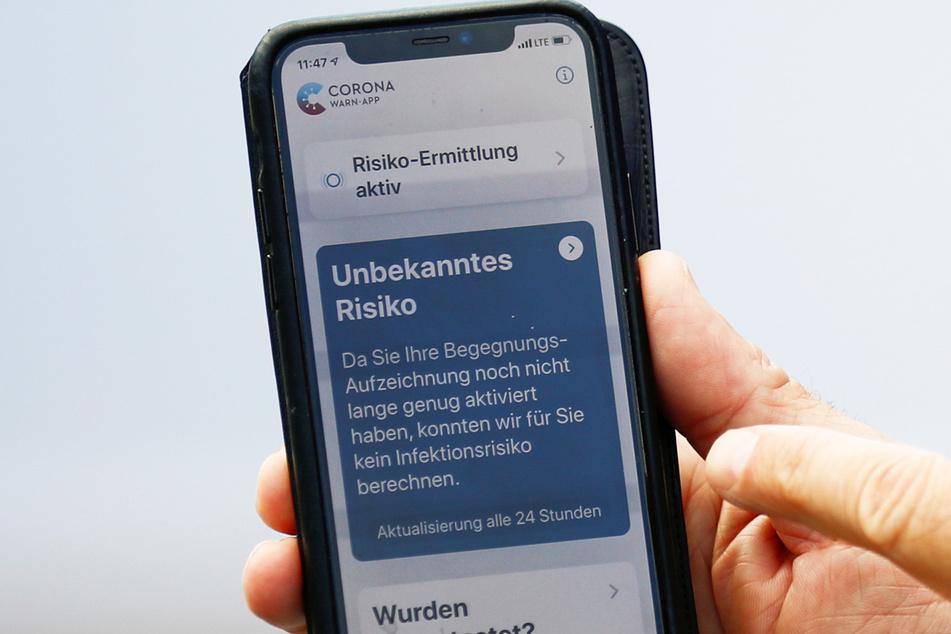 Ein Smartphone, auf dem die offizielle Corona-Warn-App zu sehen ist.