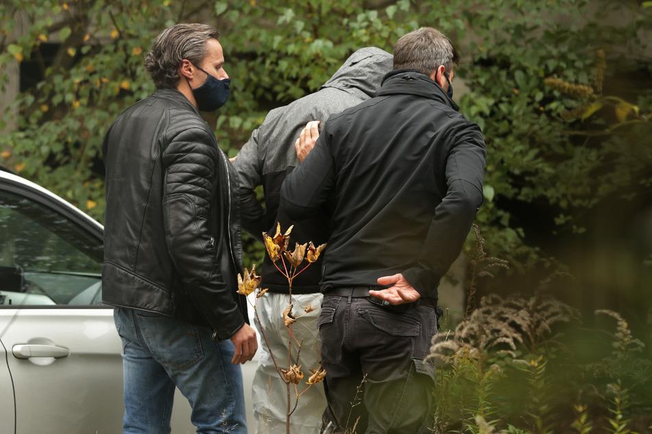 Zwei Polizisten führen einen Tatverdächtigen (M.) bei einer Begehung an den Ort, an dem ein Mädchen tot aufgefunden wurde.