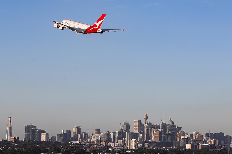 Eine Maschine der australischen Fluggesellschaft Qantas fliegt über der Stadt Sydney.