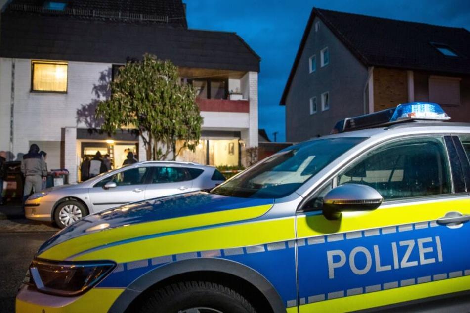 Ein Streifenwagen der Polizei parkt vor einem Mehrfamilienhaus.