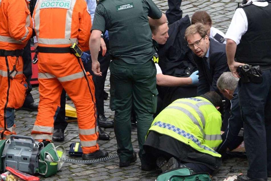 Sein Gesicht ist blutverschmiert, mit aller Macht versucht der Politiker Tobias Ellwood das Leben des Polizisten zu retten.