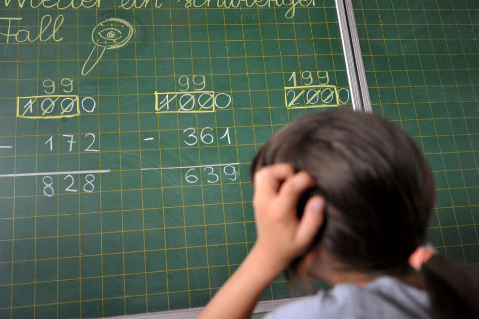 Ein Mädchen der zweiten Klasse der Grundschule steht an der Tafel vor einer Rechenaufgabe. (Symbolbild)