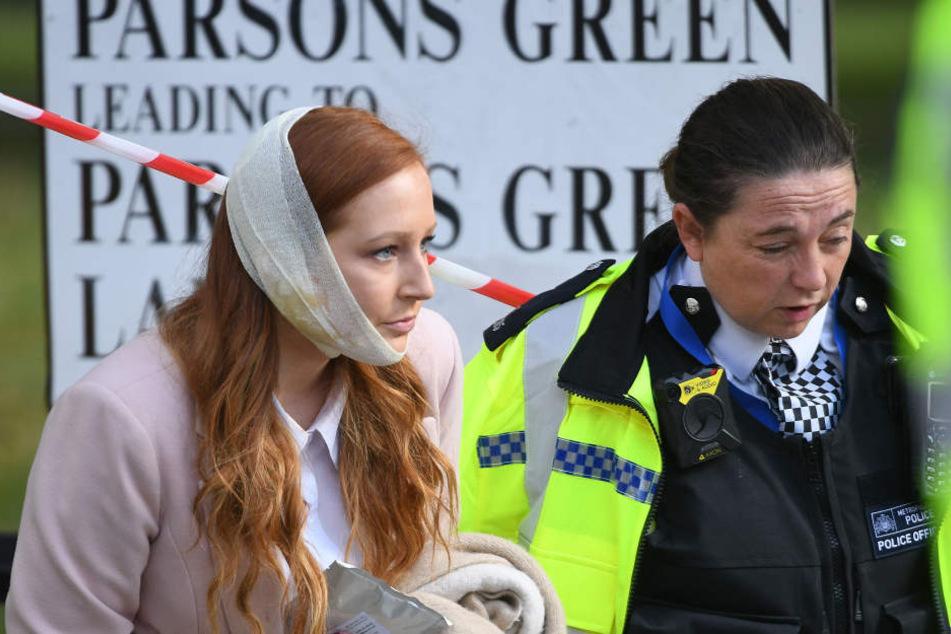 Eine verletzte Frau wird in der Nähe der U-Bahn Station Parsons Green, wo es eine Explosion gegeben hat, von einer Polizistin begleitet.