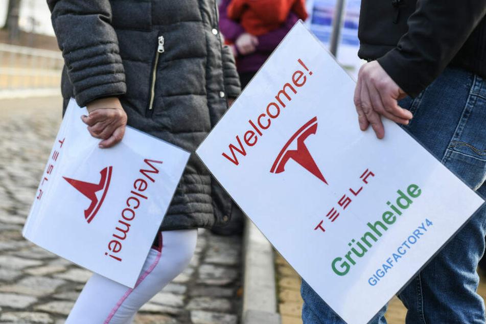 """Befürworter der Ansiedlung des US-amerikanischen Elektroautobauers Tesla halten Schilder mit der Aufschrift """"Welcome! Tesla Grünheide""""."""